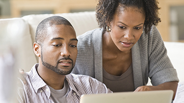 Man and woman looking at a laptop together