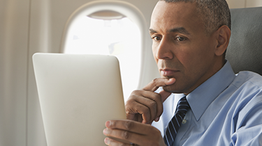 Business man looking at mobile device on an airplane