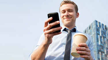 Man holding a cup of coffee and looking down at his mobile phone