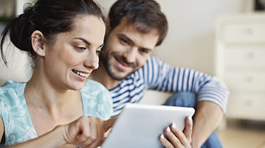 Man and woman looking at a mobile device together and smiling